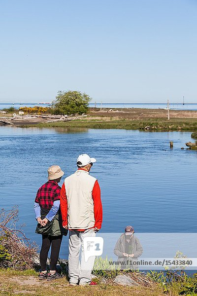 Older couple talking with a young fisherman in a tidal inlet at Steveston British Columbia.