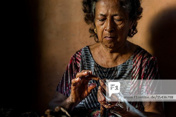 Laura Peña  a 67-years-old Salvadoran woman  applies glue on the top of a handmade cigar in her house in Suchitoto  El Salvador  30 November 2018. Hand rolled cigars have always been smoked or used for religious purposes in El Salvador. However  nowadays  due to the low profitability and general unpopularity of tobacco  the art of cigar hand rolling has practically vanished. Although Mrs. Peña has been rolling cigars for about 60 years  she claims to never smoke one. Selling a pack of 25 cigars (â.purosâ.) for 5 USD  she remains the last cigar roller in Suchitoto.