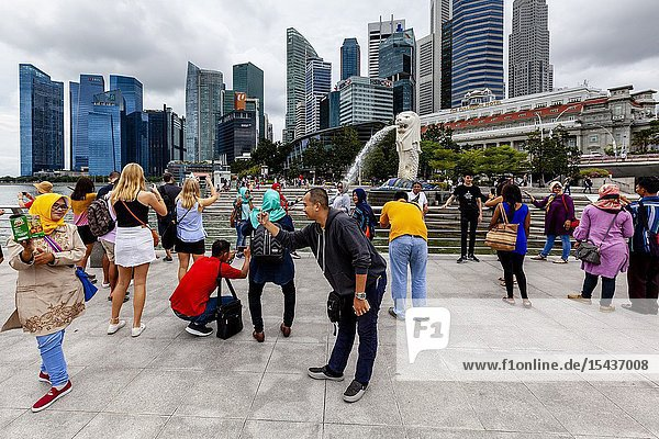 Tourists Posing For Photos In Front Of The Merlion Statue and Singapore Skyline  Singapore  South East Asia.