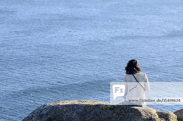 A woman looking at the end of the world at Cape Finisterre  A Coruña  Galicia  Spain
