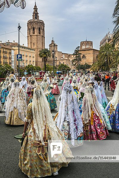 Fallas festival. Falleras. Women in traditional dress. Parade to the Plaza de la Virgin in order to make an offering of flowers to Our Lady of the Forsaken  the Patron Saint of Valencia. The celebration takes place from 4 pm until past nightfall. With all of the bunches of flowers given by the falleras to the Virgin  an impressive 15 metre-high tapestry is formed on the main façade of the Basilica and a mantle is made for the Virgin. Valencia. Valencian Community. Spain.