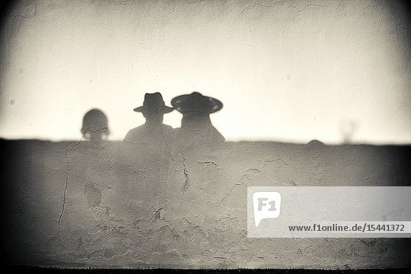 Silhouette of an unrecognizable man and woman with straw hat reflected on a wall. Mahon  Balearic Islands  Spain  Europe.