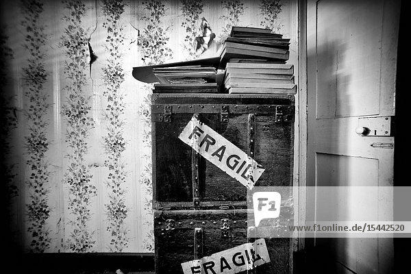 Piled up boxes and books inside a room and Fragile written on the boxes in a house. Mahon  Menorca  Balearic Islands  Spain