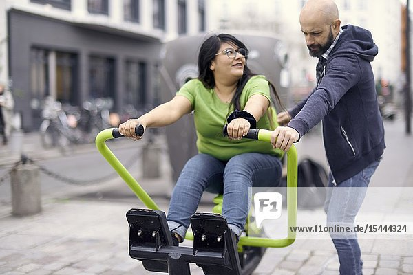 Man guiding woman on gym machine outdoors at public street  in Paris  France