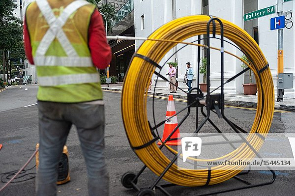 Singapore  Republic of Singapore  Asia - A worker is laying cables on a road in the central business district.