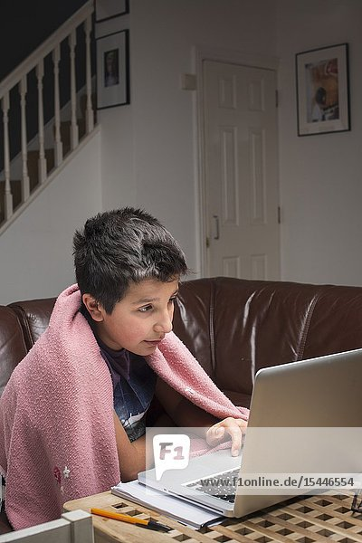 London UK. Boy  10 years old studies in his computer in a cold room.