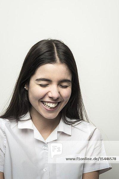 UK  teenage schoolgirl with lond dark hair having a laugh.