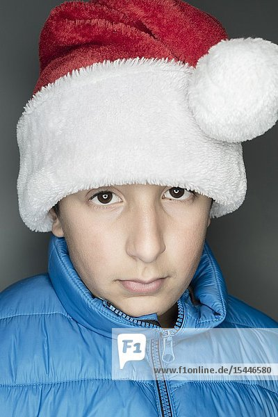 11 years old Caucasian boy in bblue jacket and Santa's hat.