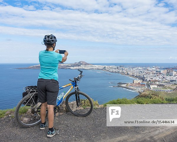 Female mountain biker on mountain overlooking Las Canteras beach and Las Palmas city on Gran Canaria  Canary Islands  Spain.