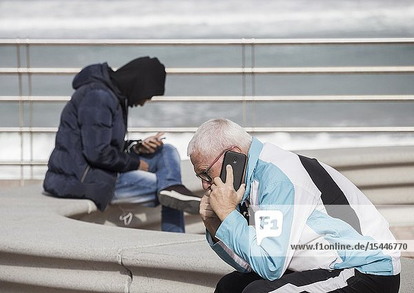 Elderly man and young man using mobile phones ovelooking city beach in Las Palmas  Gran Canaria  Canary Islands  Spain.