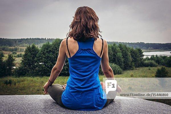 Outdoor yoga near Ozierany water reservoir near Kruszyniany village in Podlasie region of Poland.