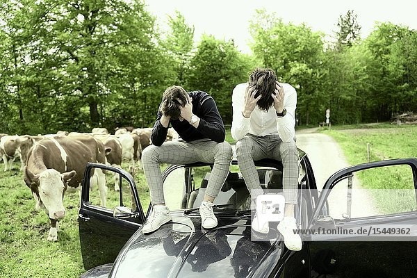 Two crestfallen young men sitting on roof of vintage car at rural countryside  in Bad T?lz  Germany