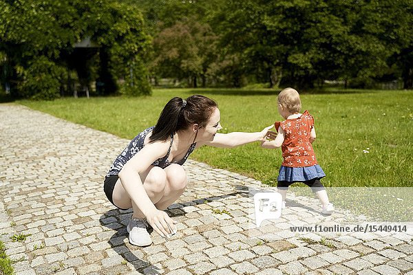 Mother holding back escaping baby toddler child in park  catching daughter