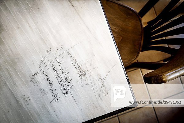 Closeup of a marble table with pencil inscriptions of a domino game  and a chair next to Mahon  Baleares  Spain  Europe.