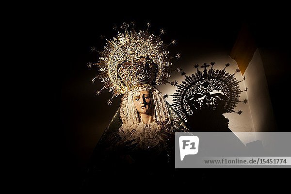 The shadow of a crowned image of the Virgin Mary is cast during Semana Santa in the church of Prado del Rey  Sierra de Grazalema  Cadiz province  Andalusia  Spain.