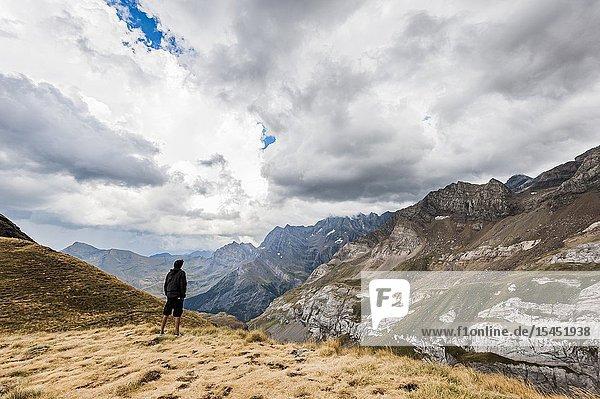 A young man wachting mountain landscape in Pyrenees national Park (Hautes-Pyrénées Department  Nouvelle-Aquitaine Region  France)