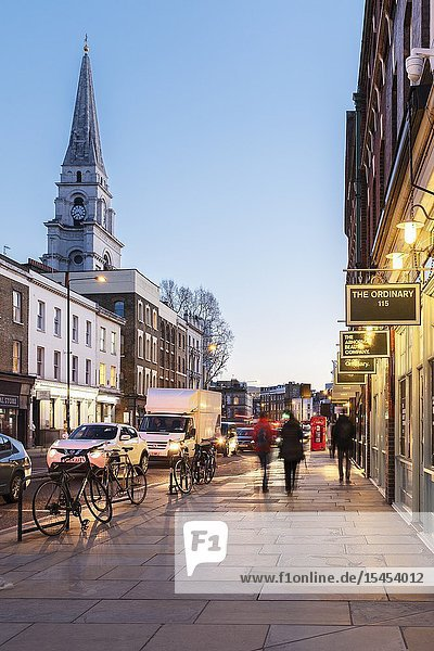 Brushfield Street  with designer shops on the South side of Spitalfieds Market and Christ Church Spitalfieds at night  London  UK.