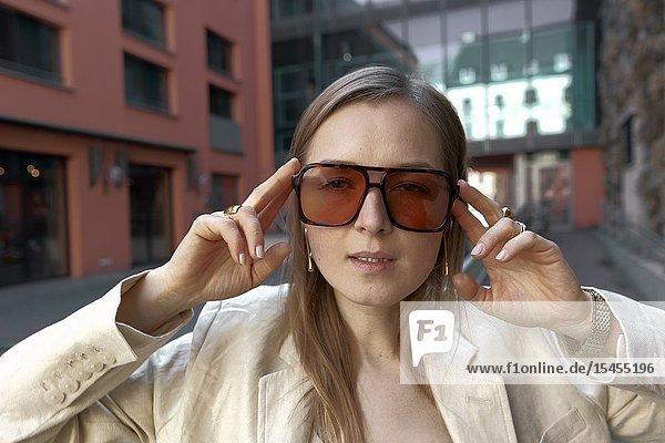 Stylish woman wearing oversized orange sunglasses