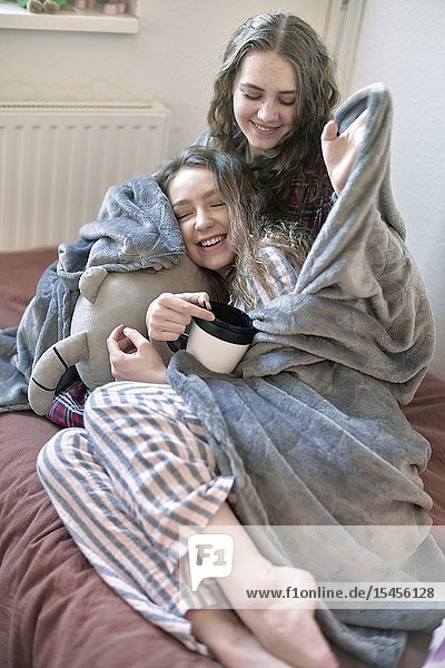 Two women enrolled in blanket  cuddling together in bed