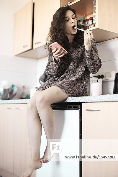 Young woman tasting spoon of coffee in kitchen at home  morning