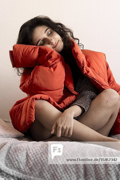 Young emotive woman sitting on bed with red winter jacket