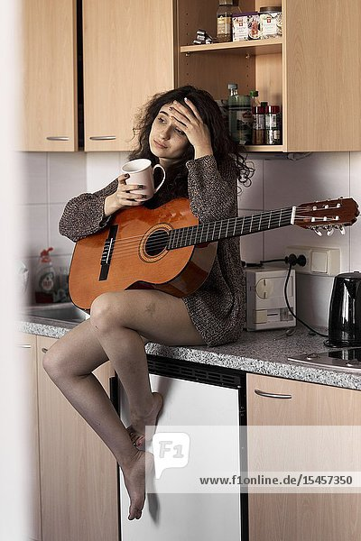 Young woman with guitar and cup in kitchen at home