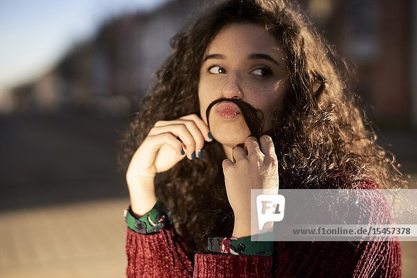 Young woman pouting with hair as moustache