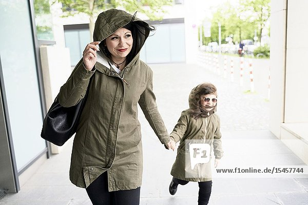 Confident single mother walking with daughter on hand in city  optimism