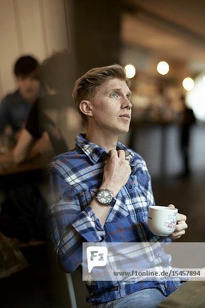 Young thoughtful man taking break in coffee shop