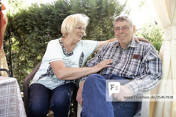 Affectionate senior couple sitting outdoors in garden