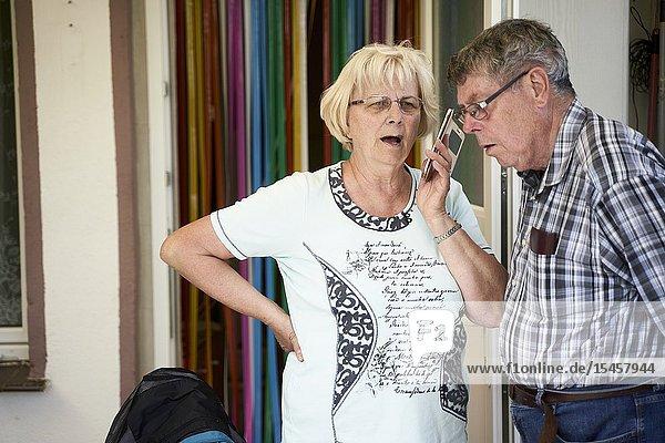 Bigoted senior woman lamenting on phone conversation  husband listening
