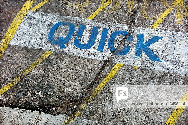 'Quick' sign painted on asphalt