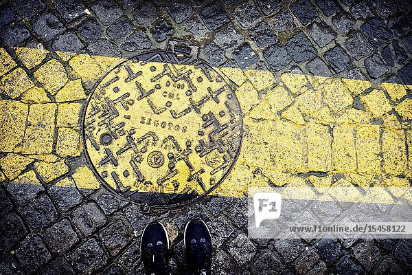 Pavement with cobblestones with a painted yellow stripe. Lisbon.