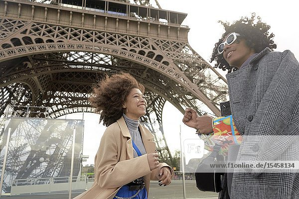 Young man and woman next to Eiffel Tower  in Paris  France