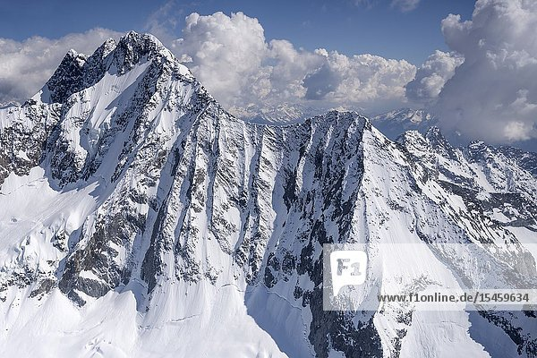 Aerial  from a small plane  of snow  ice and rocks of Disgrazia peak north side  shot in bright springtime light from Valmalenco  Sondrio  Italy.