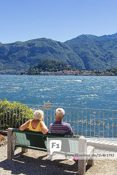 Tourists look at Bellagio from a bench on the shore of Lake Como  Lombardy  Italy.