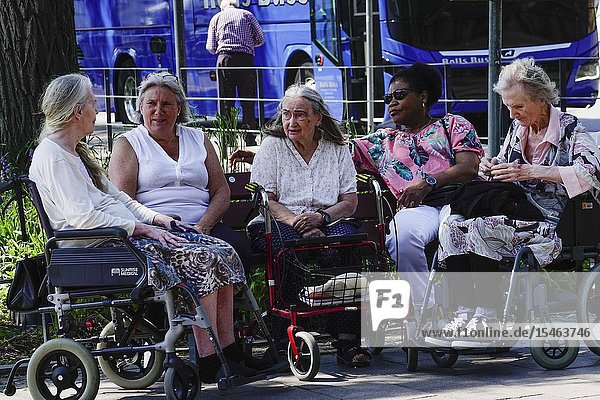 Stockholm  Sweden Senior women chatting outdors while sitting in the ír strollers and wheelchairs.