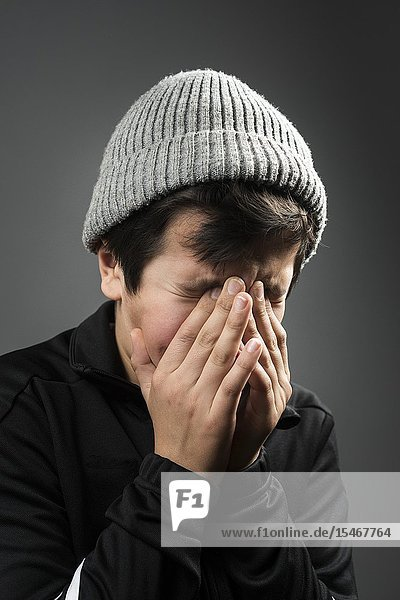 Young boy  11 years old in black tracksuit and grey wooly hat crying with his face in his hands.