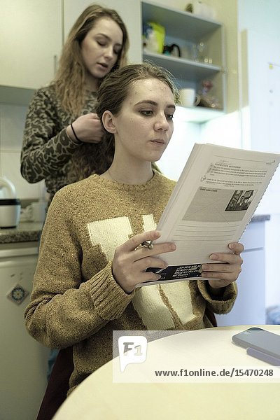 Woman learning with paper transcript in kitchen
