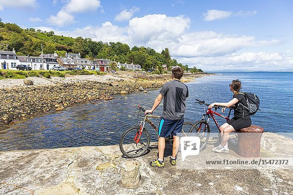 Two cyclists standing on the harbour at the small village of Sannox and looking at the view  Sannox  Isle of Arran on the Firth of Clyde  Scotland.
