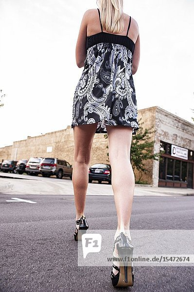 Partial view of a woman's bare legs walking on the street.