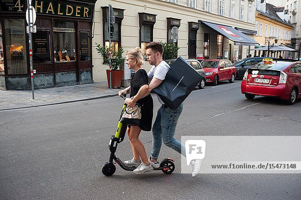 Vienna  Austria  Europe - A young couple rides an electric scooter from the e-scooter provider Hive in central Vienna.