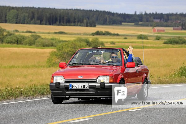 Vaulammi  Finland. August 3  2019. Family smiling and waving on 1990s red Ford Escort cabriolet on Maisemaruise 2019 car cruise. Credit: Taina Sohlman