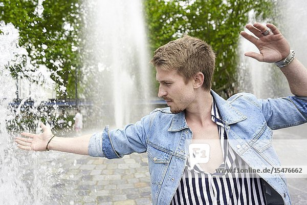 Young man at water fountain