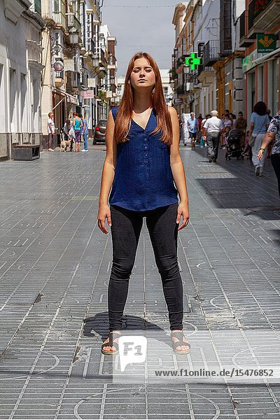 Young woman posing challenging in the middle of the street.