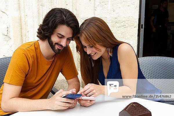 Young couple looking at the mobile on a summer terrace  smile while they wait.