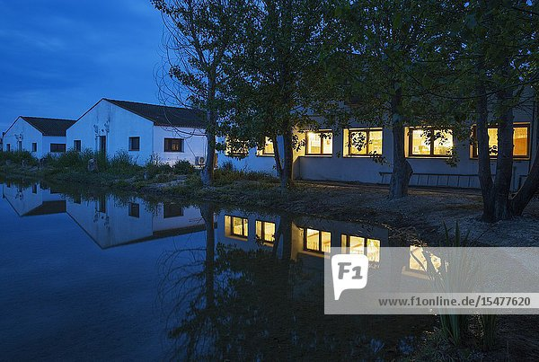 The lighted restaurant windows of the Delta Hotel at dawn. On the left the buildings with the rooms. Next to a flooded rice field. Environs of the Ebro Delta Nature Reserve  Tarragona province  Catalonia  Spain.