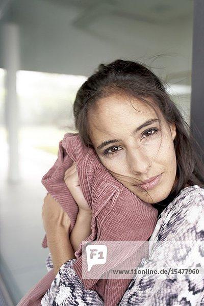 Confident woman cuddling with corduroy jacket  fashion garment