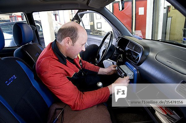 Dordrecht  Netherlands. Chief engineer and mechanic of a workshop for cars  manually installing a new sound system inside the dash of a vehicle.