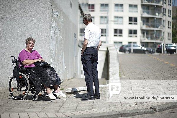 Rotterdam  Netherlands. Woman in Wheel chair talking to a walking neighbor on the sidewalk of her neighborhood  residential street.